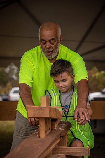 Workshop participant Ed Sabir helps an aspiring timber framer.